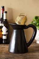 Lifestyle image of the Black Brown Terracotta Jug - Small with utensils in it on corwded wooden shelf with pale wall background