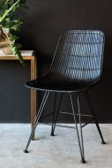 black rattan dining chair on dark background lifestyle image