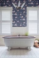 lifestyle image of Cole & Son New Contemporary - Flamingos Wallpaper - 4 Colours Available with white shutters and roll top bath on white tiled floor