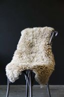 lifestyle image of Genuine Sheepskin Rug - Curly Beige on black wooden chair with dark wall background