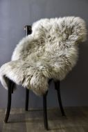 lifestyle image of genuine sheepskin rug - silky light grey on black chair on wooden flooring and grey wall background