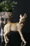 lifestyle image of Grace The Gold Deer Coin Bank on black table with plant in face pot behind and dark wall background