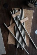 Lifestyle image of the Pack Of 20 Silver Grey Paper Straws With Gold Glitter Tags