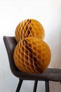 Image of the Set Of 2 Honeycomb Ball Decorations In Mustard Gold on a chair