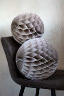 Image of the Set Of 2 Honeycomb Ball Decorations In Stone Grey on a chair