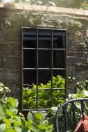 Lifestyle image of the Indoor Or Outdoor Windowpane Mirror on dark brick wall in outside setting