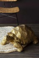 Lifestyle image of the Gold Tortoise ornament with mandala rug rattan chair and dark flooring and wall background