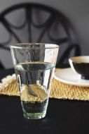 lifestyle image of Le Verre Beldi Recycled Glass Highball on set table with Natural Wicker Placemat With White Tassels and black dining chair with dark grey wall background