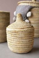 lifestyle image of the Small Moroccan Wicket Basket with lid on the top and other baskets in background and grey pom pom blanket and grey flooring and pale wall background