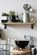 lifestyle image of oak shelf with cast iron brackets - small in crowded kitchen with white wall background