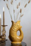 Lifestyle image of the Amber Ceramic Gluggle Jug with faux stems