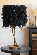 Lifestyle image of the Antique Gold Bird Leg Table Lamp With Black Feather Shade