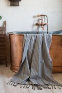 Close-up lifestyle image of the Black Striped 100% Cotton Hammam-Style Bath Towel With Fringe draped over the bath