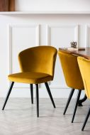 Lifestyle image of Golden Ochre Deco Velvet Dining Chair on a white panelled wall background