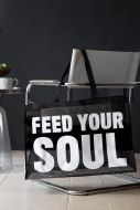 Lifestyle image of the feed your soul large shopper bag on grey chair with dark wall background