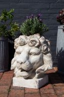 Front on lifestyle image of the Large Rustic Stone Effect Lion Head Planter