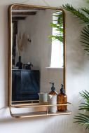 Lifestyle image of the Light Gold Tall Bathroom Mirror With Shelf on a light background