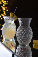 Image of one empty Pikes at Rockett St George Cosmic Pineapple Cocktail Glass and one full