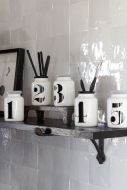 Lifestyle image of the Set Of 5 Vintage Style Numbered White Display Bottles on a shelf