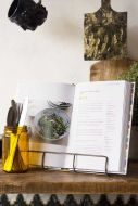 Lifestyle image of the Antique Brass Finish Wire Cookbook Holder with cookbook inside on crowded wooden shelf