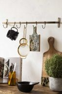 Lifestyle image of the Antique Bronze Finish Hook Rail on a crowded wooden shelf with white wall background