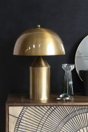 lifestyle image of Gold Dome Table Lamp on black side table with dark wall background