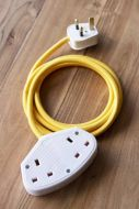 lifestyle Image of the Stylish 2m Extension Cable - Yellow Lead With White Sockets on pale wooden floor background