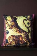 Lifestyle image of the Two Leopards Velvet Cushion on black bench with dark wall background