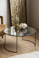 Lifestyle image of the Vintaged Glass Mirror & Iron Round Coffee Table on pale wooden floor with coral and vase on table