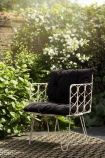 Lifestyle image of the front of the Bamboo Link Armchair With Black Noir Seat Cushion in garden background
