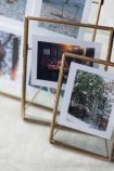 lifestyle image of Brass & Glass Framed Desk Top Picture Frames - 5x7 Portrait with other frames on pale wooden surface