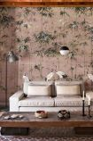 Lifestyle image of the Chinoiserie Wallpaper Mural - Garzas Rose Pink with pale sofa with floor lamp and ceiling light above it and wooden coffee table with ornaments on