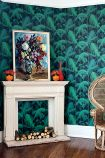 lifestyle image of Cole & Son Contemporary Restyled - Palm Jungle Wallpaper - Emerald Green 95/1003 - SAMPLE with white fireplace with art frame on top and woven chair