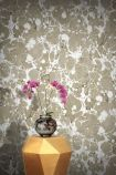lifestyle image of feathr neural wallpaper - sand with gold side table and vase with pink flowers in