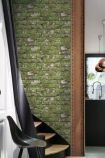 lifestyle image of Koziel Moss White Brick Wallpaper next to staircase and black chair under window and copper ceiling light in background