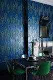 lifestyle image of Matthew Williamson Peacock Wallpaper with black dining table and green chairs and fireplace with mirror hung on wall above