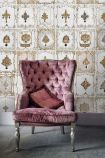 Lifestyle image of the neutral shade of Anna's Jewellery wallpaper with pink velvet armchair in front of it on grey flooring