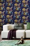 lifestyle image of mind the gap sci-fi pulp wallpaper with white sofa with purple blanket and green cushions and green rug with copper effect sitting man ornament on floor