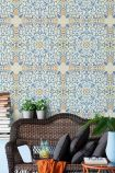 lifestyle image of Mind The Gap Spanish Tile Wallpaper with brown bench and plants with dark cushions and orange blanket