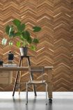 lifestyle image of NLXL TIM-06 Timber Strips Wallpaper by Piet Hein Eek with wooden table with plant on black stool and wooden chair in front