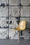 lifestyle image of NLXL TIN-01 Brooklyn Tin Tiles Wallpaper By Merci with yellow chair on grey flooring