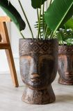 Image of the Large Giant Clay Face Flower Pot with the smaller on in the background with a chair